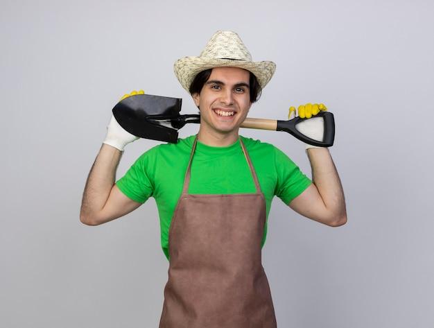 Sorridente giovane giardiniere maschio in uniforme indossando guanti e cappello da giardinaggio tenendo la vanga dietro al collo