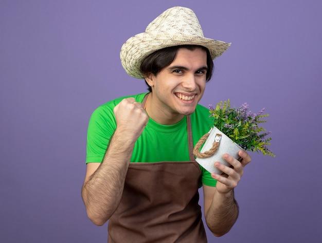 Sorridente giovane giardiniere maschio in uniforme che indossa cappello da giardinaggio tenendo il fiore in vaso da fiori che mostra sì gesto isolato sulla porpora