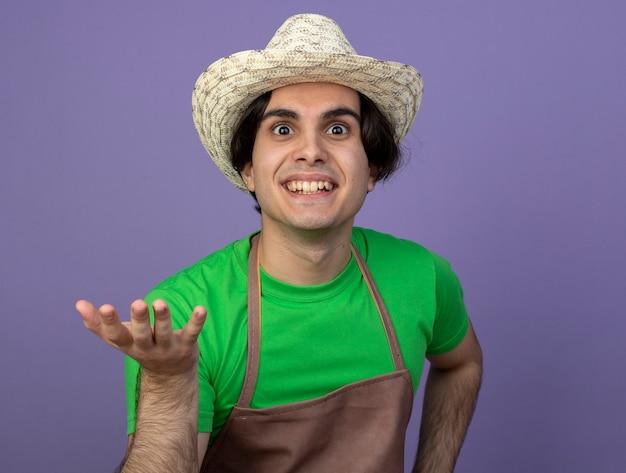 Sorridente giovane giardiniere maschio in uniforme che indossa il cappello da giardinaggio tendendo la mano alla macchina fotografica isolata sulla porpora