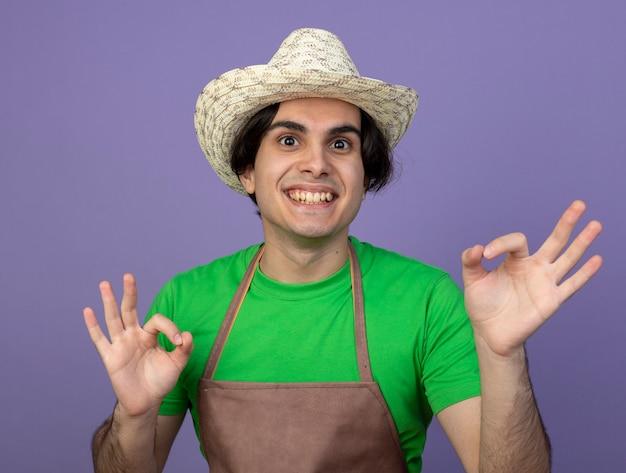 Sorridente giovane giardiniere maschio in uniforme che indossa il cappello di giardinaggio che mostra il gesto giusto isolato sulla porpora
