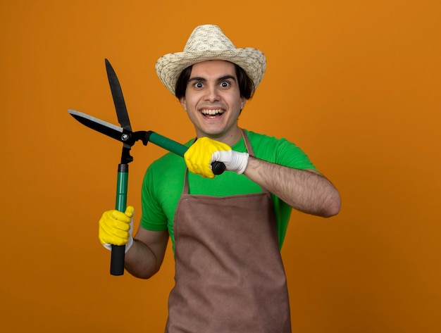 Smiling young male gardener in uniform wearing gardening hat with gloves holding clippers isolated on orange wall