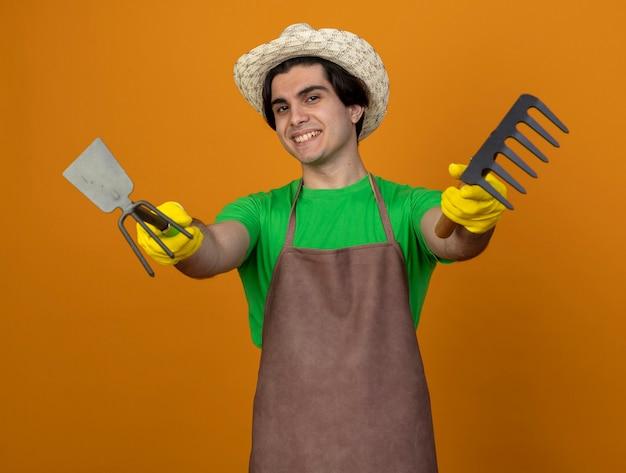 Sorridente giovane giardiniere maschio in uniforme che indossa il cappello da giardinaggio con guanti tenendo fuori zappa rastrello con rastrello isolato sulla parete arancione