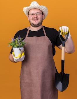 オレンジ色の壁に分離された植木鉢の花とスペードを保持している園芸帽子と手袋を身に着けている若い男性の庭師の笑顔