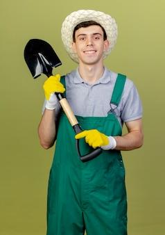 ガーデニング帽子と手袋を身に着けている笑顔の若い男性の庭師は、コピースペースでオリーブグリーンの背景に分離されたカメラを見てスペードを保持します。