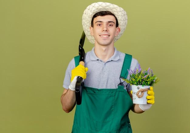 Sorridente giovane giardiniere maschio indossando guanti e cappello da giardinaggio tiene vanga e fiori in vaso di fiori
