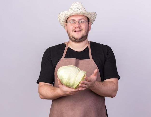 白い壁に分離されたキャベツを保持している園芸帽子をかぶって若い男性の庭師の笑顔