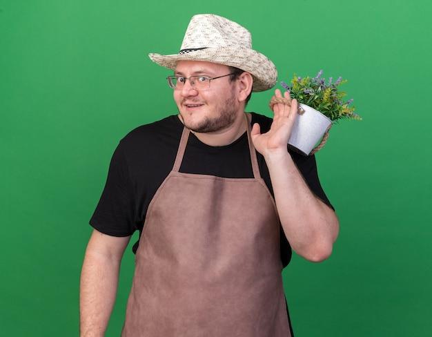 Sorridente giovane giardiniere maschio che indossa cappello da giardinaggio tenendo il fiore in vaso di fiori sulla spalla isolato sulla parete verde
