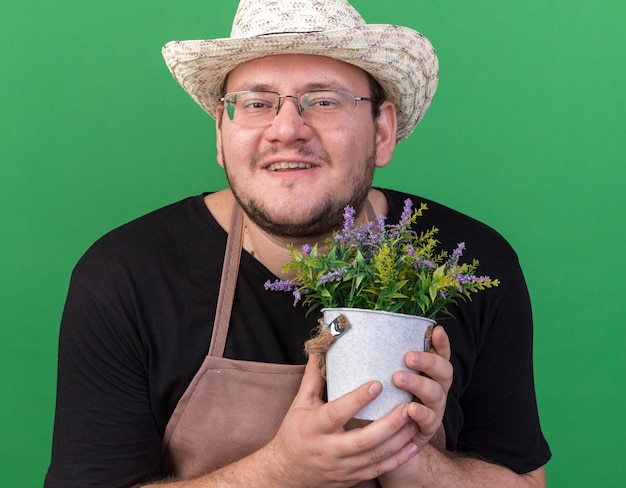 緑の壁に分離された植木鉢の花を保持しているガーデニング帽子を身に着けている若い男性の庭師の笑顔