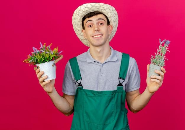 コピースペースとピンクの背景に分離された植木鉢を保持しているガーデニング帽子をかぶって若い男性の庭師の笑顔