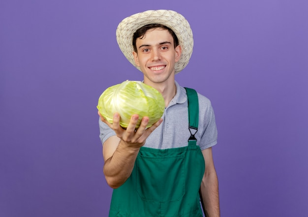 ガーデニング帽子をかぶって笑顔の若い男性の庭師はキャベツを保持します