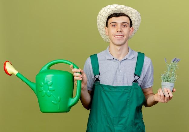 Il giovane giardiniere maschio sorridente che porta il cappello di giardinaggio tiene i fiori in vaso di fiori e annaffiatoio