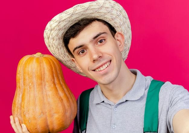 ガーデニング帽子をかぶって笑顔の若い男性の庭師は、カボチャを保持し、コピースペースでピンクの背景に分離されたカメラを保持するふりをします