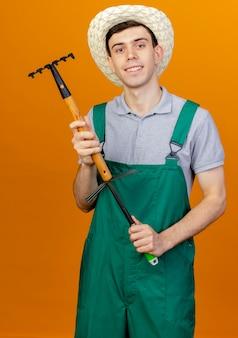 Улыбающийся молодой мужчина-садовник в садовой шляпе держит грабли над граблями мотыги, изолированными на оранжевом фоне с копией пространства