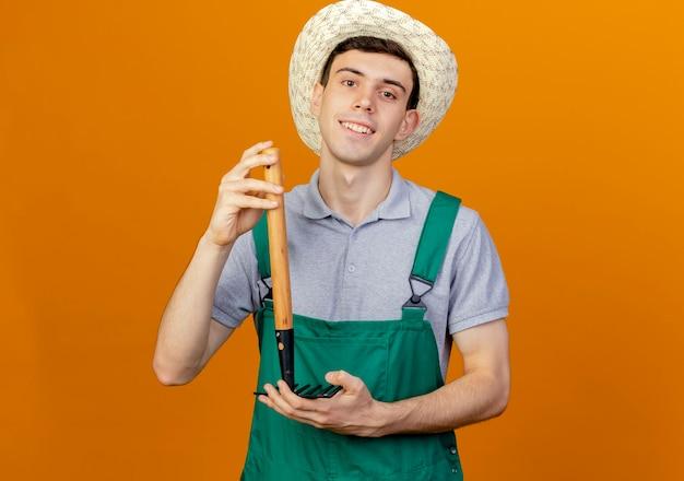 Улыбающийся молодой мужчина-садовник в садовой шляпе держит грабли вверх ногами