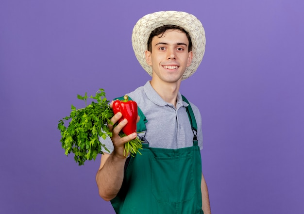 Il giovane giardiniere maschio sorridente che porta il cappello di giardinaggio tiene il peperone rosso e il coriandolo