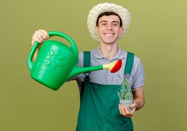 Sorridente giovane giardiniere maschio che indossa il cappello da giardinaggio finge di innaffiare i fiori in vaso di fiori con annaffiatoio