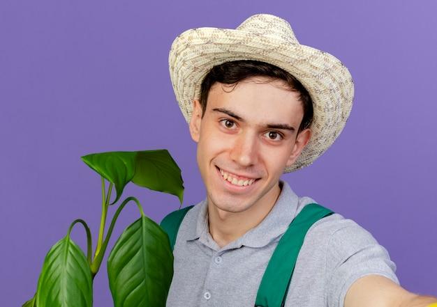 園芸帽子をかぶって笑顔の若い男性の庭師は、カメラを保持するふりをして植物と立っています