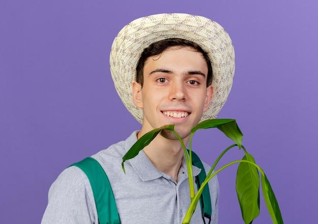 ガーデニング帽子をかぶって笑顔の若い男性の庭師は植物と立っています
