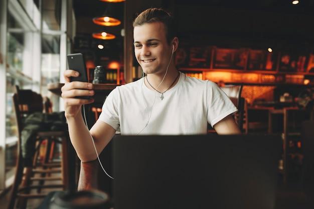 이어폰에 노트북에 앉아 어두운 우아한 카페에서 휴대 전화 화면을보고 흰 셔츠에 웃는 젊은 남성