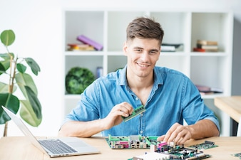 Smiling young male IT technician with hardware equipment's