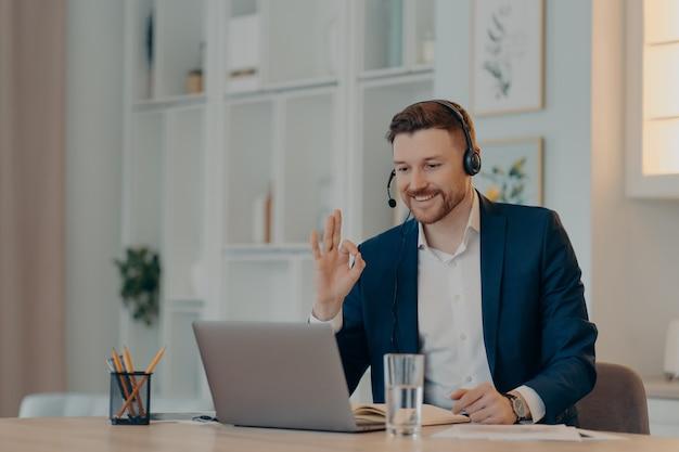Улыбающийся молодой офисный работник мужского пола в гарнитуре смотрит на экран ноутбука и показывает знак ок или жест ок, сидя в роскошном офисе и имея онлайн-видеозвонок Premium Фотографии