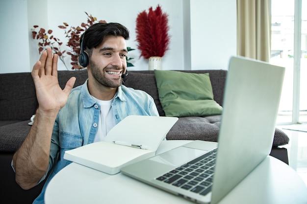 Улыбающийся молодой мужчина на своем ноутбуке, оператор телефонного центра разговаривает с клиентами через наушники