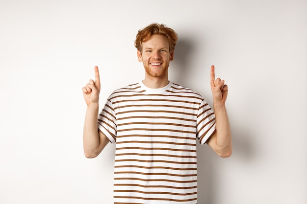 Smiling young male student with red hair showing logo, pointing fingers up and looking happy, standing over white background.