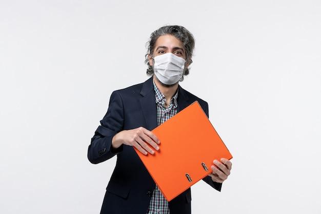 Sorridente giovane maschio in tuta e tenendo i suoi documenti indossando la sua maschera chirurgica su una superficie bianca