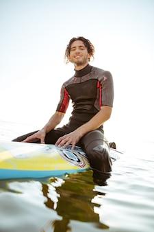 수영복을 입고 물에 자신의 서핑 보드에 앉아 정면을보고 웃는 젊은 남성 서퍼