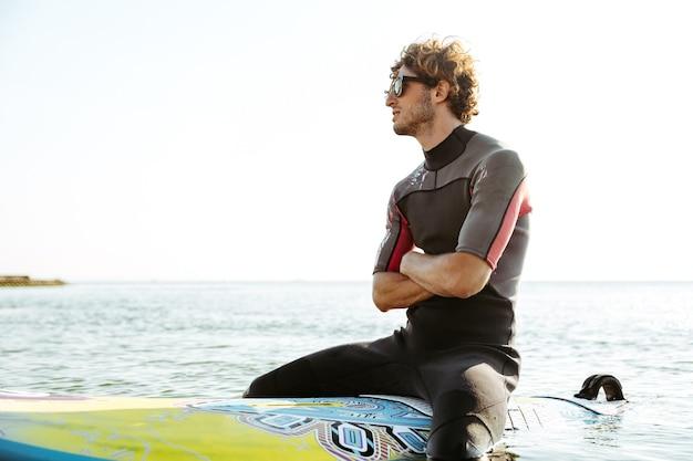 손으로 자신의 서핑 보드에 앉아 웃는 젊은 남성 서퍼가 수영복을 입고 바다에 교차
