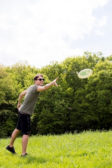 Smiling young male throwing plate for frisbee on meadow