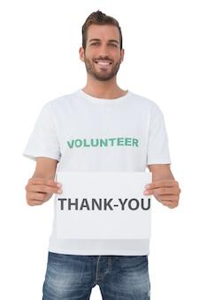 「ありがとう」紙を持っている若い男性ボランティアを笑って