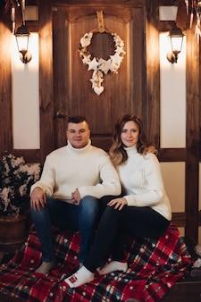 Улыбающийся молодой мужчина и женщина, взявшись за руки, сидя на крыльце дома с рождественскими украшениями на нем.