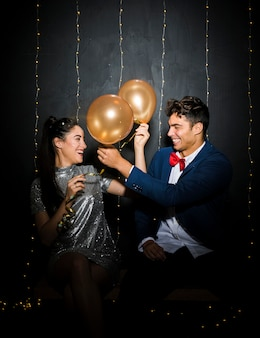 Smiling young man and woman with balloons on bench