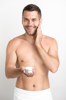 Smiling young man applying face cream looking at camera standing against white background