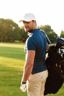 Smiling young man in cap holding golf bag