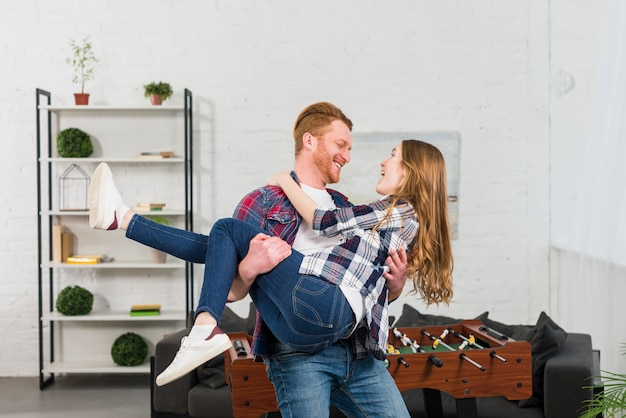 Smiling young man carrying her girlfriend in front of table soccer in the living room