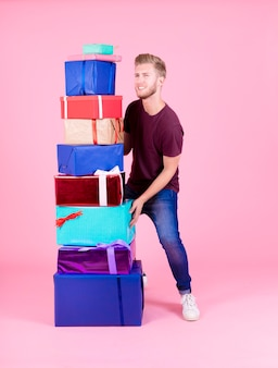 Smiling young man carrying stack of colorful presents against pink background