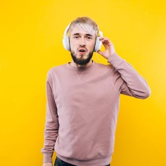 웃는 젊은 남자 캐주얼 옷을 입고 노란색 배경에 서, 한쪽을 보여주는