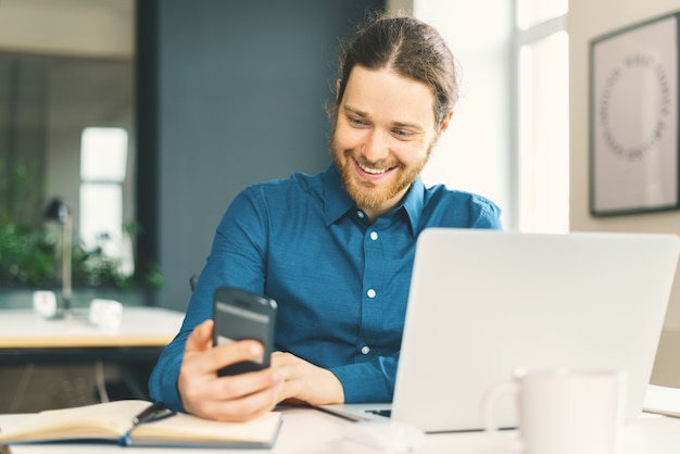 Smiling young man in casual wear looking at smartphone screen at workplace