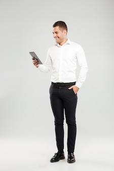 Smiling young man chatting by tablet computer.