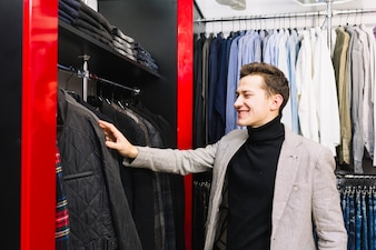 Smiling young man checking the clothes in the rack
