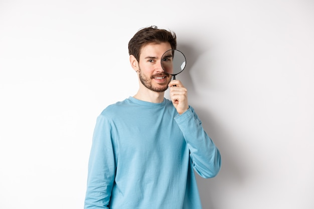 Smiling young man detective looking through magnifying glass, searching for promo offer, standing on white background.