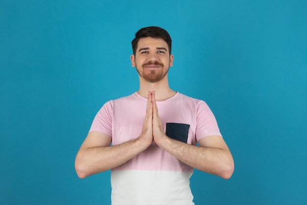 Smiling young man doing meditation on a blue.