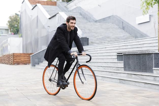 Улыбающийся молодой человек, одетый в пальто, катается на велосипеде по улице