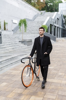 Улыбающийся молодой человек, одетый в пальто, гуляет с велосипедом по улице
