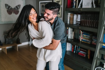 Smiling young man embracing her girlfriend standing in front of bookshelf