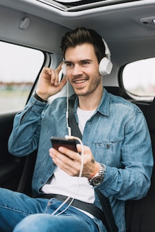 Smiling young man enjoying the music on headphone attached to cellphone