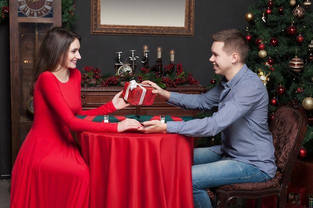 웃는 젊은 남자가 아름다운 여자에게 매력적인 선물을 제공합니다.
