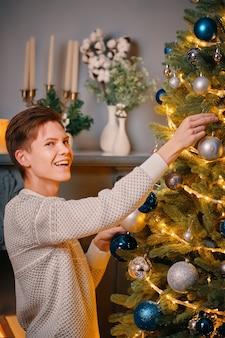 笑顔の若い男は、クリスマスツリーのカラフルな装飾と明るい花輪に銀のボールを掛けます...